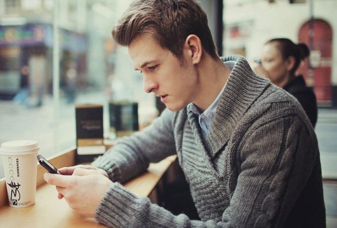 Парень читает в телефоне