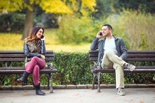 Парень с девушкой говорят по телефону