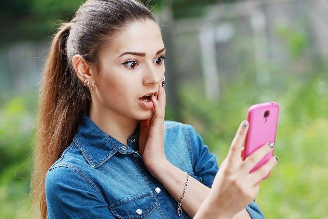 Девушка читает переписку в телефоне