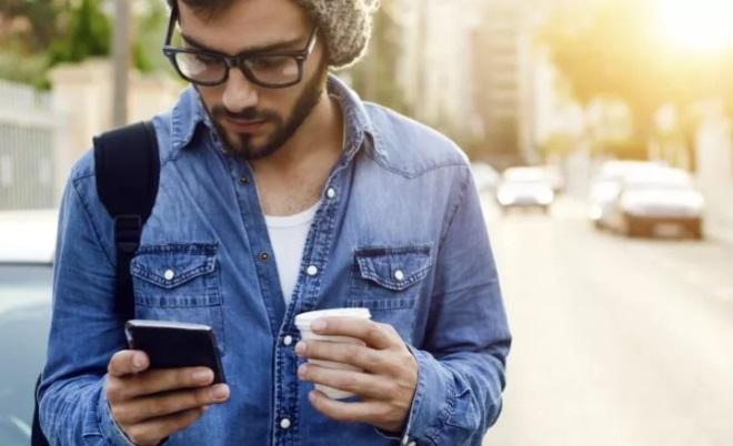Парень читает сообщения в телефоне